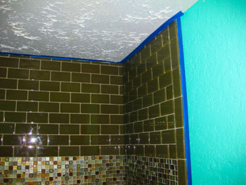 A glass tile wall with an accent strip