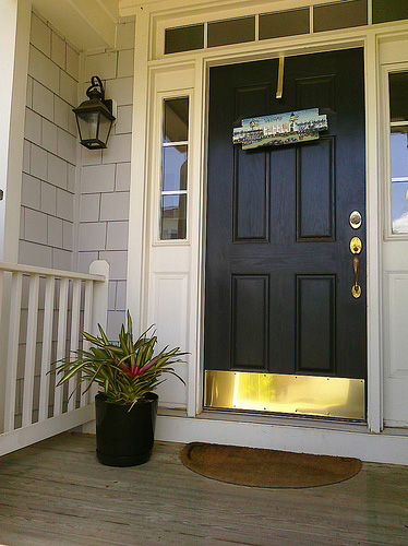 An entry door with brass kick plate, photo courtesy Michelle Rebecca