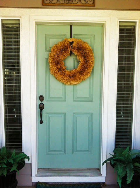 A light blue front door with wreath