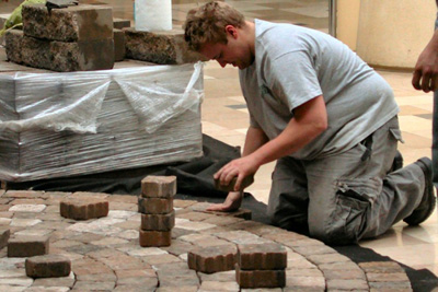 Installing concrete pavers; photo courtesy Jzlomek