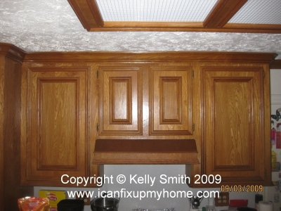 Kitchen wall cabinets and exhaust fan installed over electric range