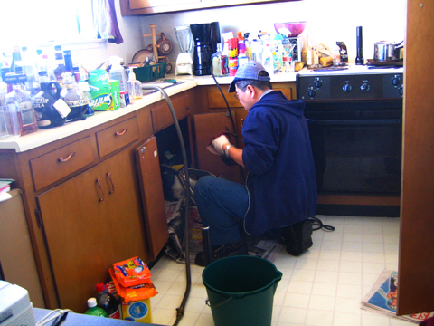 A plumber clearing a drain; image courtesy Rick
