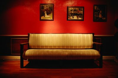An antique yellow couch in a red room